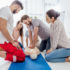 group of people looking at man performing cpr on dummy during first aid training