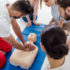 instructor performing cpr on dummy during first aid training with group of people